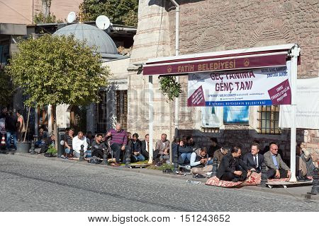 Modern Turkish Men sitting at Street preparing to Traditional Midday Mohammedan Prayer Ceremony. Istanbul, Turkey, November 20, 2015