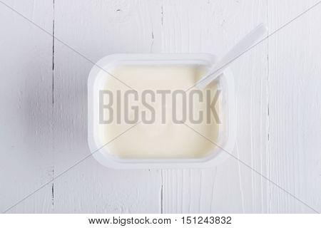Creamy yogurt. Greek yogurt. Yogurt in white plastic cup. Natural yogurt.