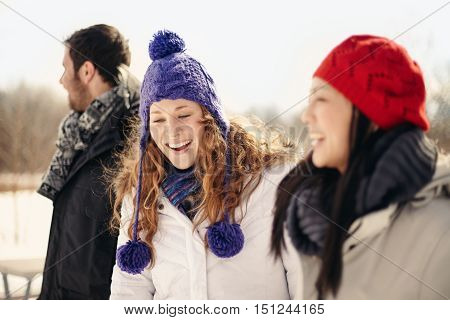 Group of millenial young adult friends enjoying wintertime in a snow filled park