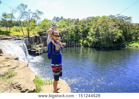 Young Father With Daughter On His Shoulders Enjoying Kerikeri Waterfall