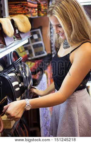 A pretty blonde female looking at merchandise in a shopping mall