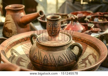 Souvenirs of clay pots for food with relief ornament on Sunday clearance sale