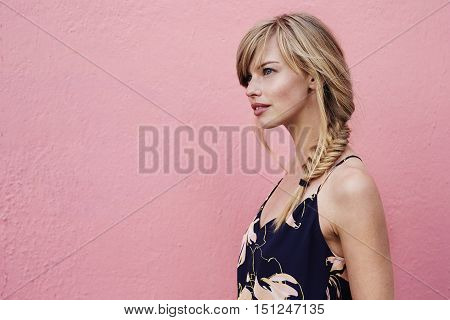 Gorgeous blond woman against pink background side view