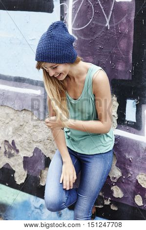 Laughing lady in vest and hat looking down