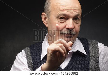 Elderly man threatens with a finger. Shaking finger, angry at work