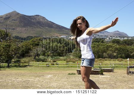 Caucasian female farm girl balancing on a beam in a field