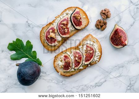 Figs toast with walnut and honey on marble table