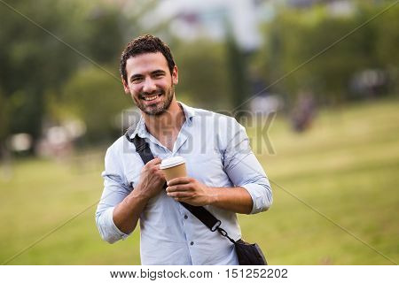 Young businessman is drinking coffee and resting from work at the park.