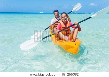 Father with his daughter kayaking at tropical ocean