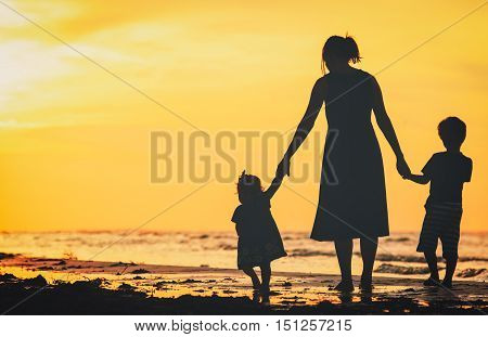 mother and two kids walking on beach at sunset sky