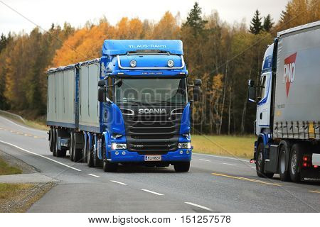 KAARINA, FINLAND - OCTOBER 9, 2016: Blue Scania R580 combination vehicle of Kosti Saukko Oy meets another Scania transport truck on the road on a cloudy day in autumn.