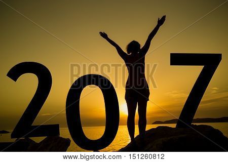 Happy new 2017 year card. A girl standing on a rocky shore watching the sunset standing as a part of 2017 sign