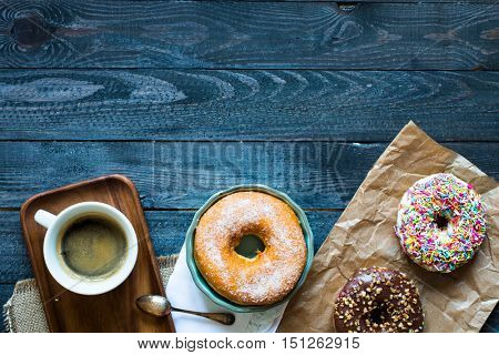 Colorful Donuts and coffee breakfast composition with different color styles of doughnuts over an aged wooden desk background.