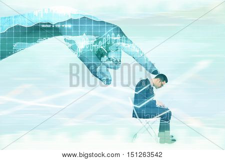 Abstract digital hand contolling young businessman with laptop on abstract background with business charts. Control concept