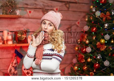 surprised young woman wearing knitted warm sweater and scarf in christmas time. Shocked blond female on xmas.