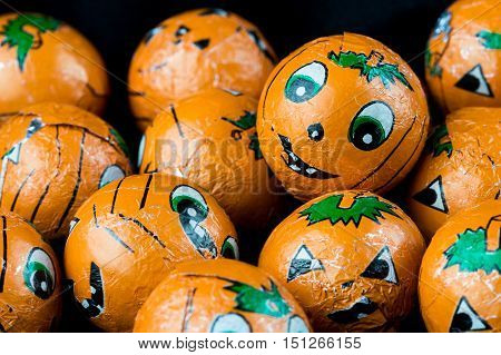 Close up of Halloween Jack-o-lantern foil covered sweets. Ready to hand out to Trick or Treaters.