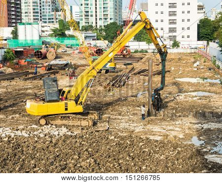 Yellow excavator is working on construction site.
