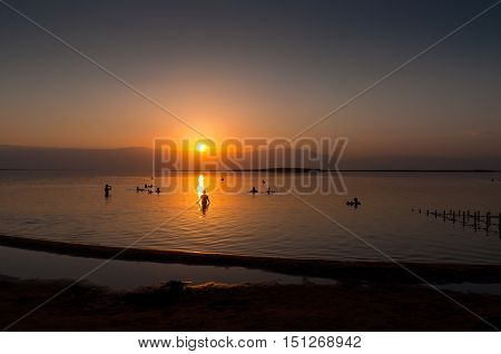 Dead Sea is a salt lake in Israel. Its shores are the lowest point on the surface of the Earth on dry land. The lake is very salty (around 30% salt) causing people to float on its waters.