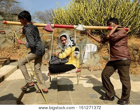 PALITANA GUJARAT INDIA - JANUARY 25: Indian pilgrims carried on primitive sedan chairs to the holy Palitana top in the Gujarat state in India Palitana in January 25 2015
