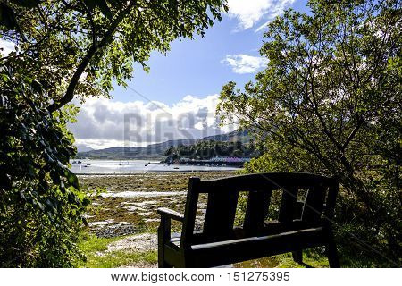 Bench with a view to the coloful buildings on the harbor at Portree the largest town on the Isle of Skye in the Inner Hebrides Scotland