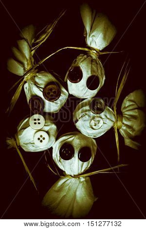 Five Halloween dolls with button eyes with heads close together in a circule over dark background. Trick or treaters