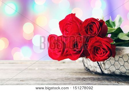 Five fresh red roses in basket on grey wooden background