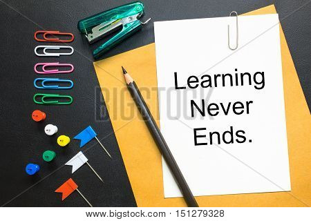 Learning never ends Text on white paper / business concept