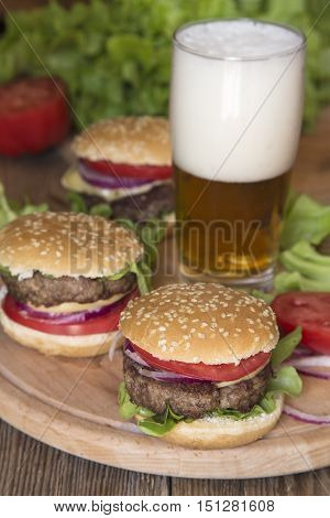 Mini burgers with the fresh vegetables and a glass of beer