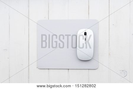 White wireless mouse on a mouse pad, top view