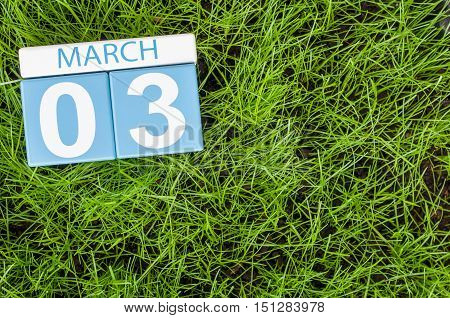 March 3rd. Day 3 of month, calendar on football green grass background. Spring time, empty space for text.