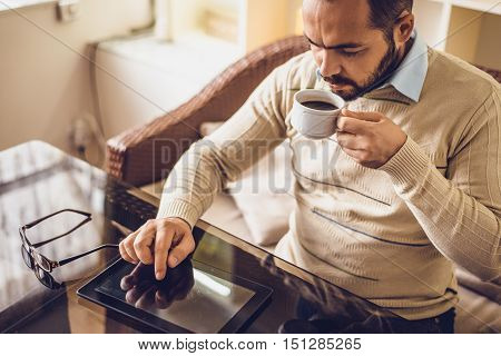 a man sitting in a cafe with tablet. Casual Man Using Tablet Computer Sitting in Cafe Surfing Internet