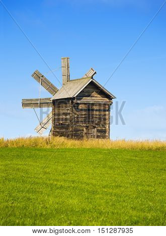 Karelia Kizhi Russia - August 2015: Traditional wooden windmill on Kizhi Island. Wooden churches at background. Karelia Russia