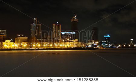 Winter cityscape with frozen Iset River. Yekaterinburg. December. Ancient two-storeyed house is in the foreground and skyscrapers are on the background. Yellow and blue fires of streetlights. The plain surface of ice on a city pond is strewn lightly with