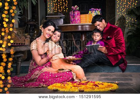 Indian young Family arranging diyas on rangoli on diwali festival night, people and diwali