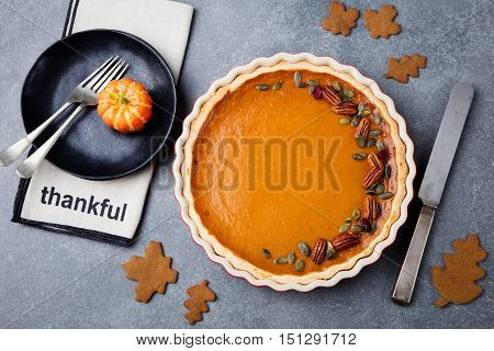 Pumpkin pie, tart made for Thanksgiving day in a baking dish. Grey stone background. Top view