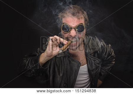 Angry steampunk smoking man with goggles on smoking a cuban cigar