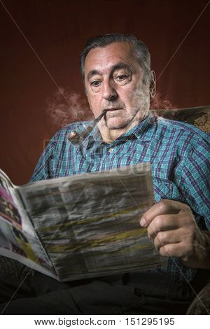 Senior man shocked with news he's reading, smoking a pipe and sitting in his armchair