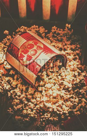 Retro striped red and white snackfood container spilling out vintage popcorn. Classic hollywood cinema details