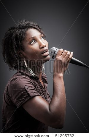 Beautiful African woman singing with the microphone. Picture with high contrast effect.