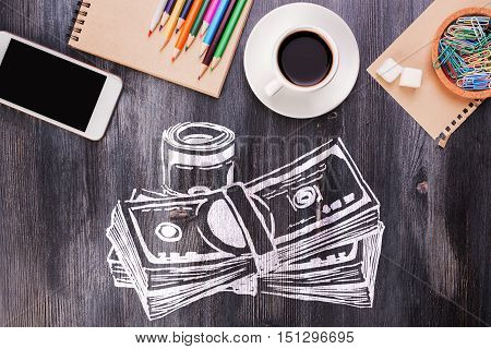 Wooden desktop with creative money sketch coffee cup blank smartphone supplies and other items