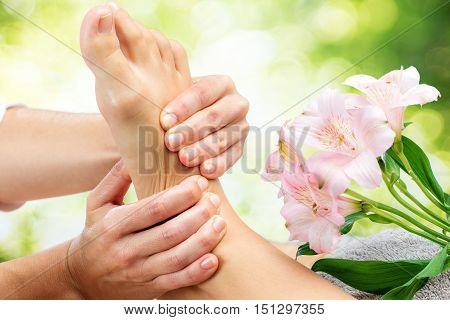 Macro close up of therapist doing healing foot massage against green background.