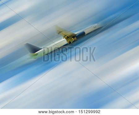 The airplane in the blue sky with clouds blurred in postproduction