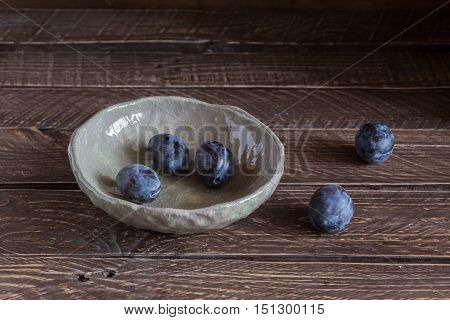 ceramic bowl with plums plums in a clay bowl plums on a brown background.