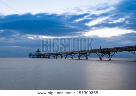 Long exposure landscape image of sea and pier with the soft light at sunset Clevedon Somerset England UK