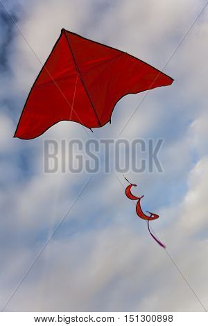Red kite flying in blue sky with clouds