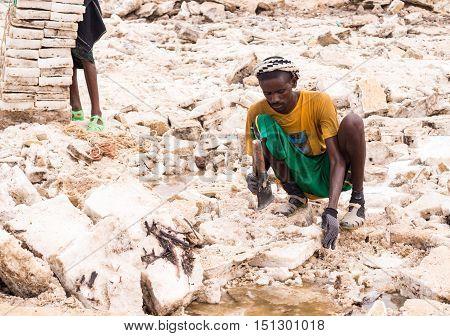 DANAKIL DEPRESSION ETHIOPIA - JUNE 29 2016: Afar man mining salt from salt flats in Afar region Danakil Depression Ethiopia.