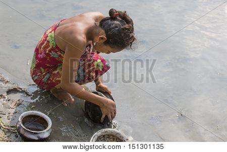 Chittagong Bangladesh February 25th 2016: young bangladeshi woman washing dishes in a river