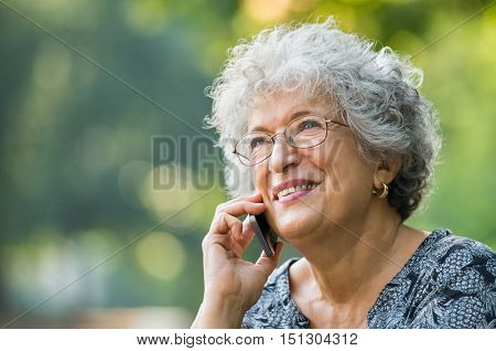Portrait of mature woman talking on smartphone outdoor. Senior woman smiling and talking on the phone at park. Close up face of a cheerful elderly woman on phone call.