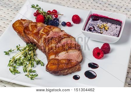 Grilled Meat With Sauce And Berries On A Square White Plate