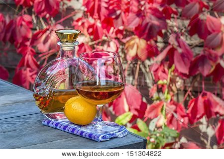Bottle and a snifter of brandy with lemon on the old table in autumn garden
